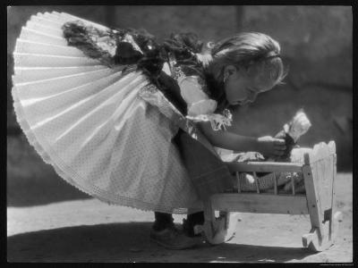 Young Romanian Girl Leans to Pick up Her Small Doll from a Beautifully Crafted Wooden Crib--Photographic Print