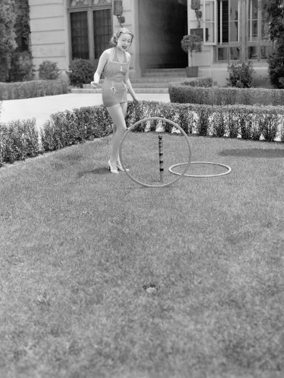 Young Woman in a Sun Suit Playing with Rings in the Yard--Photo