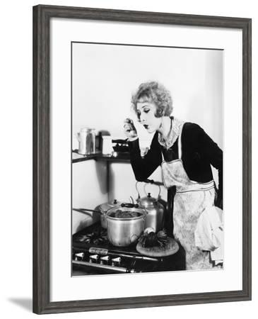 Young Woman in an Apron in Her Kitchen Tasting Her Food from a Pot--Framed Photo