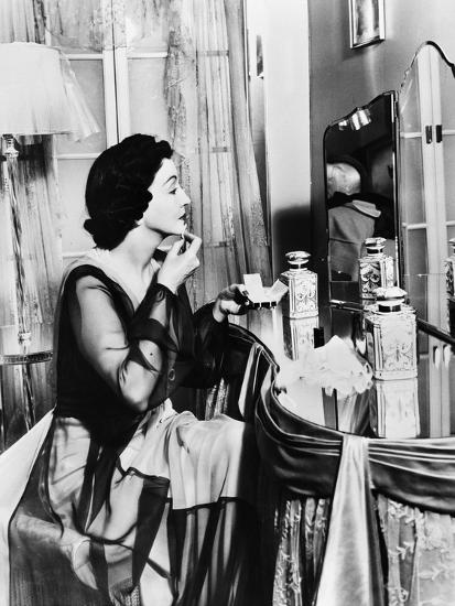 Young Woman Looking into a Mirror and Putting on Make Up--Photo