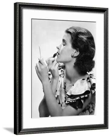 Young Woman Looking into a Mirror and Putting on Make Up--Framed Photo
