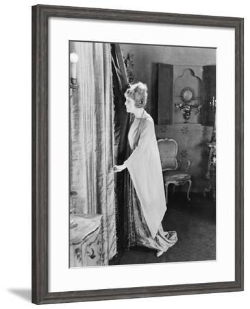 Young Woman Looking Out from Behind Her Curtains--Framed Photo