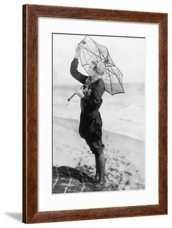 Young Woman on the Beach with an Umbrella Looking Like a Spider Web--Framed Photo