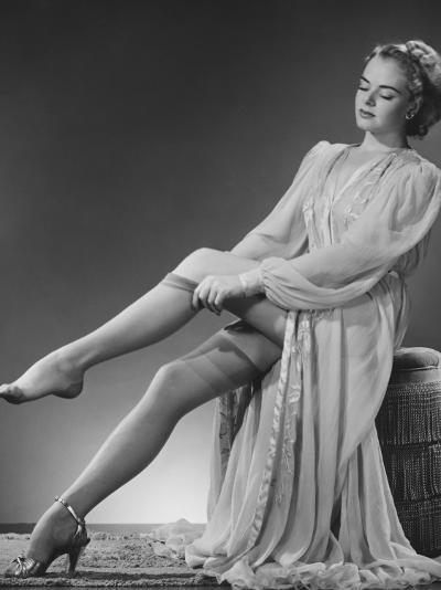 Young Woman Putting on Stockings in Studio-George Marks-Photographic Print