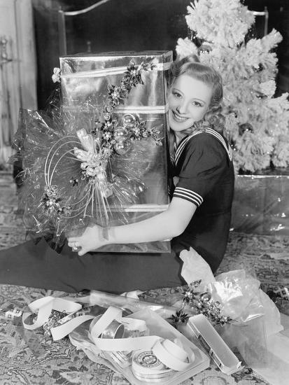 Young Woman Sitting in a Living Room Hugging a Present on Christmas Day--Photo