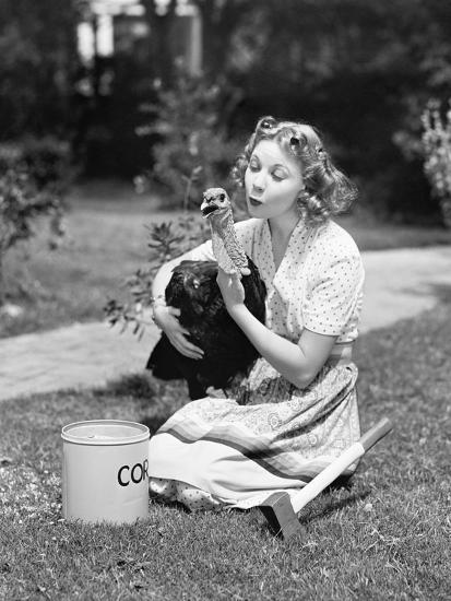 Young Woman, with an Ax Next to Her, Hugs a Turkey--Photo