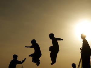 Youths Play on a Trampoline at Sunset in the Neighborhood of Islamabad, Pakistan