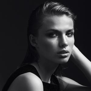 Black and White Portrait of a Beautiful Girl in the Studio on a Black Background, the Concept of Be by Yuliya Yafimik