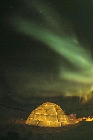 Churchill, Manitoba, Canada. Northern Lights shine above lit igloo.