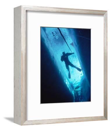 Man Diving in Water Between Ice